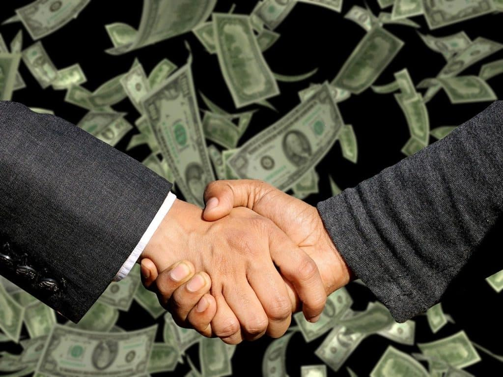 לחיצת יד ודולרים ברקע